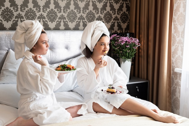 Amigos disfrutando de su día de spa con comida deliciosa.