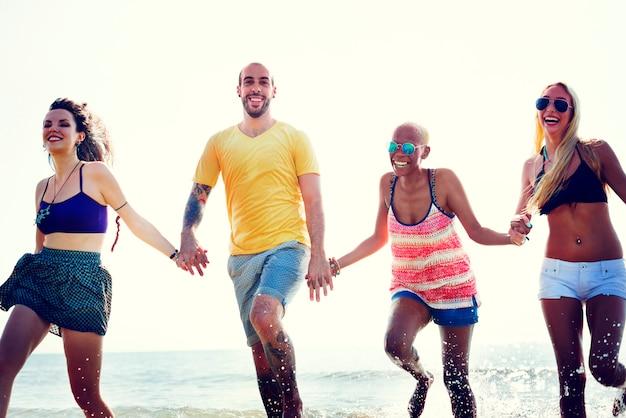 Amigos diversos del verano de la playa que llevan a cabo concepto de las manos