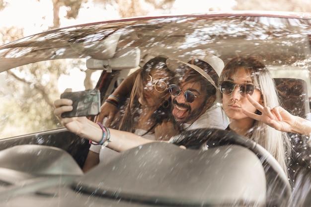 Amigos divertidos tomando selfie dentro del coche en el teléfono móvil