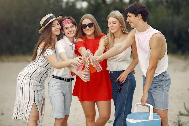 Los amigos se divierten en la playa con bebidas