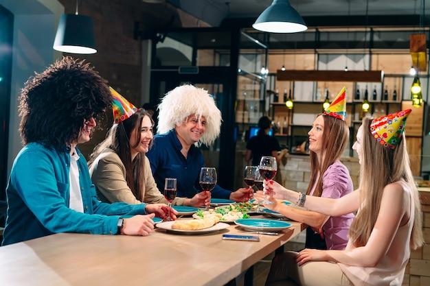 Los amigos se divierten en un restaurante y beben vino.