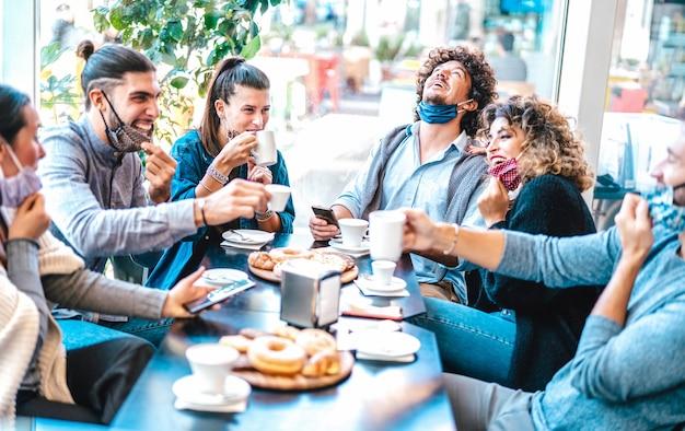 Amigos divirtiéndose bebiendo y comiendo en la cafetería