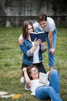 Amigos divirtiéndose con libros en el parque