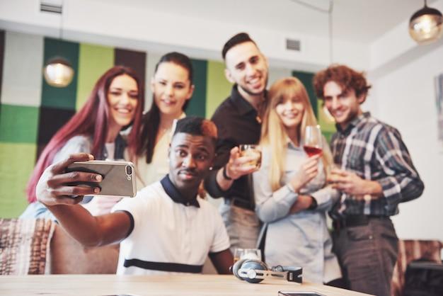 Amigos divirtiéndose y haciendo selfie en restaurante