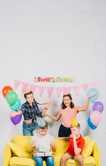 Amigos divirtiéndose mientras niño sentado en el sofá con regalos de cumpleaños