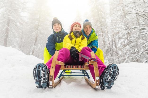 Amigos divirtiéndose en la nieve deslizándose con un pequeño trineo.