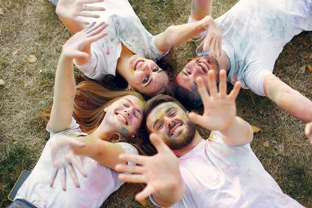 Amigos divirtiéndose en un parque con pinturas holi