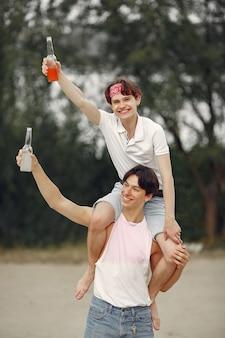 Amigos divirtiéndose en una playa con bebidas