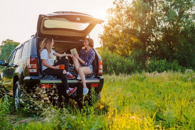 Amigos divirtiéndose sentado en el maletero