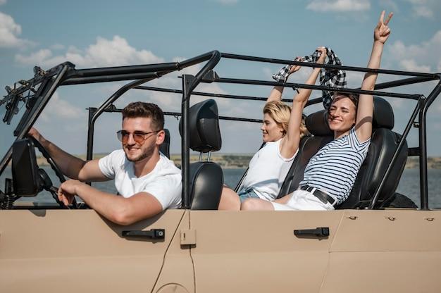 Amigos divirtiéndose y viajando juntos en coche.
