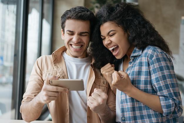 Amigos emocionados con smartphone jugando videojuegos celebración éxito
