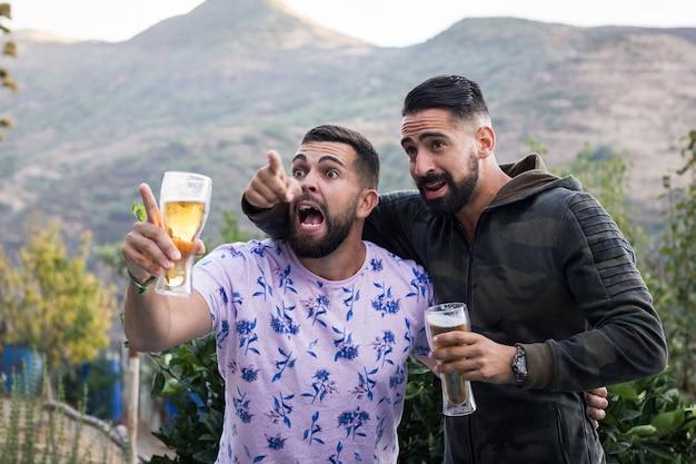 Amigos emocionados sosteniendo cervezas en la terraza del bar hombres jóvenes viendo deportes en la televisión fanáticos entusiastas