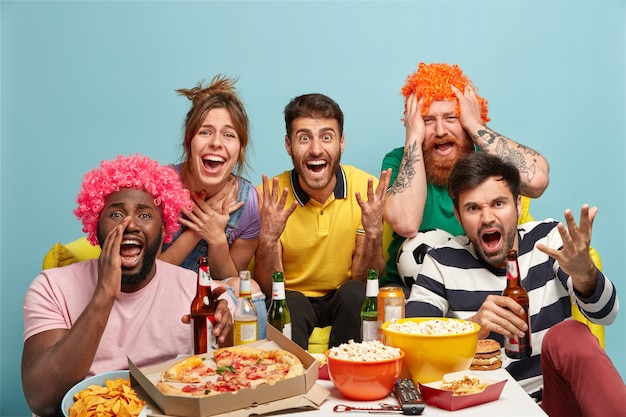Amigos, entretenimiento en el hogar, concepto de tiempo libre. los mejores amigos multiétnicos emocionales disfrutan de la transmisión de tv, están conectados a internet inalámbrico, comen bocadillos y palomitas de maíz, están suscritos al cable o satélite