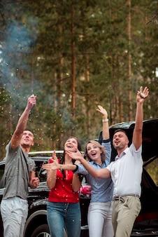 Amigos entusiastas que celebran al aire libre