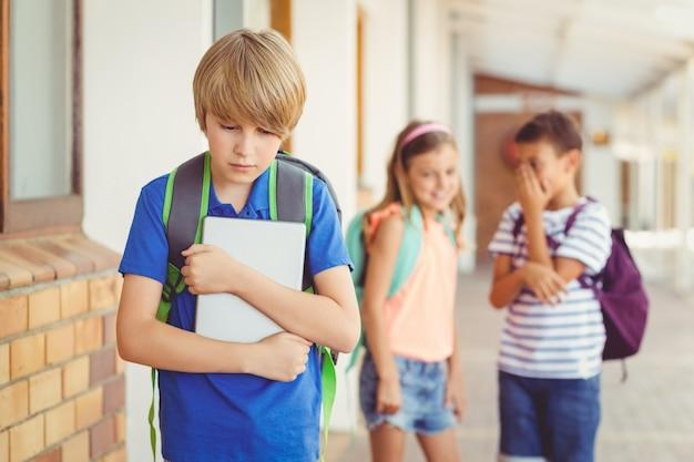 Amigos de la escuela intimidando a un niño triste en el corredor