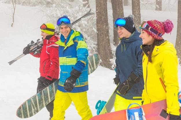 Amigos con esquí y snowboard caminando sobre la nieve.