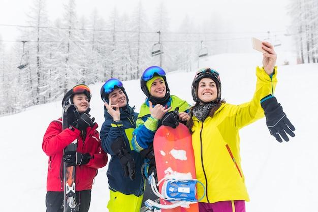 Amigos con esqui y snowboard tomando autofotos en las pistas.
