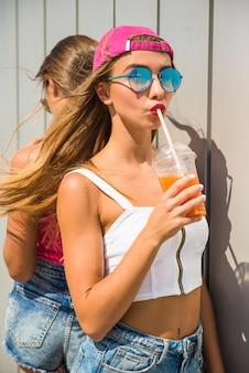 Los amigos están de pie el uno al otro y beben jugo.