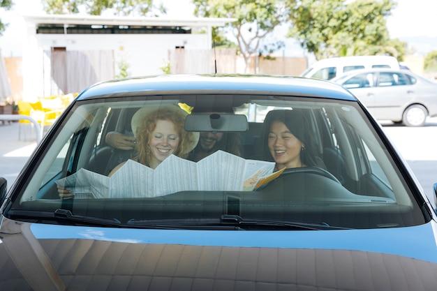 Amigos explorando el mapa mientras están sentados en un auto en una estación de servicio