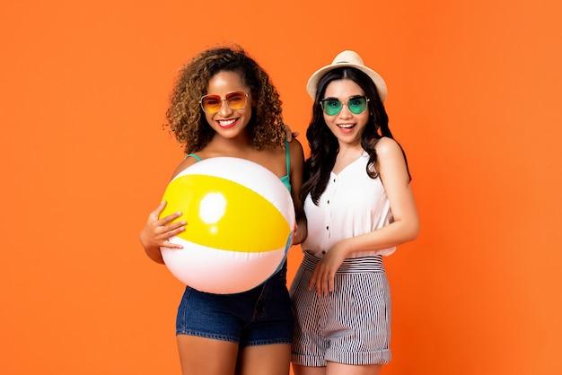 Amigos felices afroamericanos y asiáticos de la mujer con la bola de playa colorida