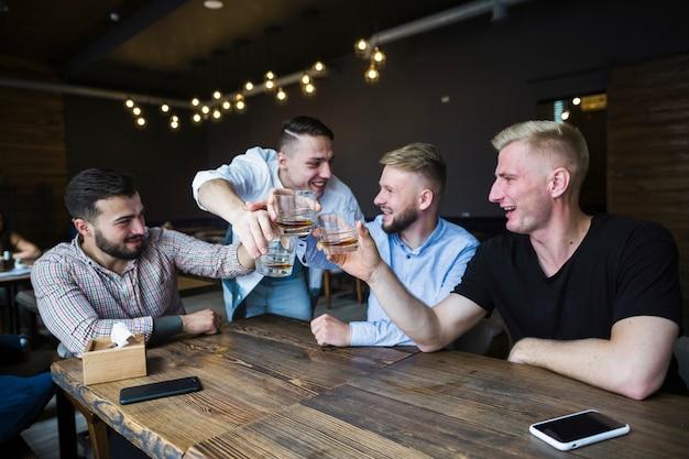 Amigos felices animando con vasos de whisky en el bar