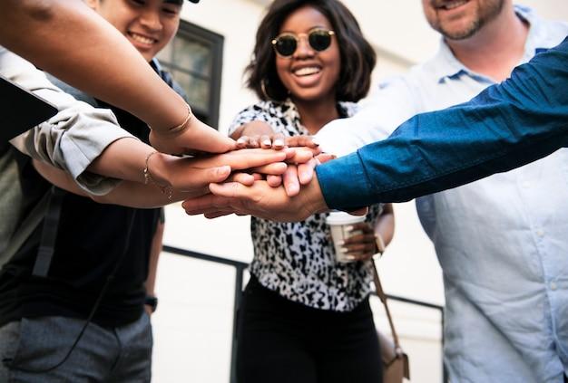 Amigos felices apilando sus manos durante una reunión