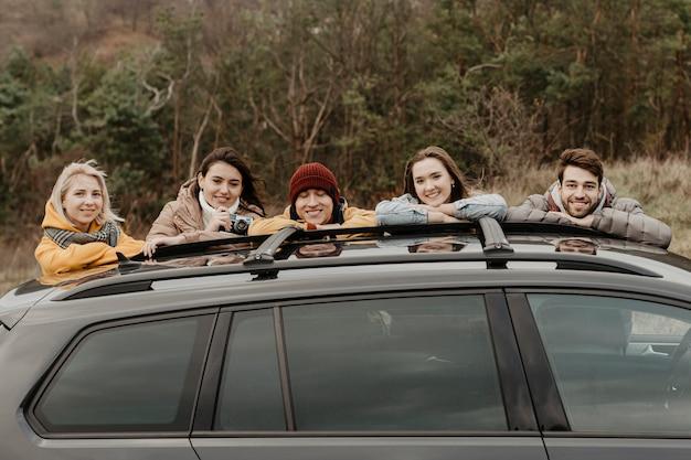 Amigos felices, apoyándose en el coche