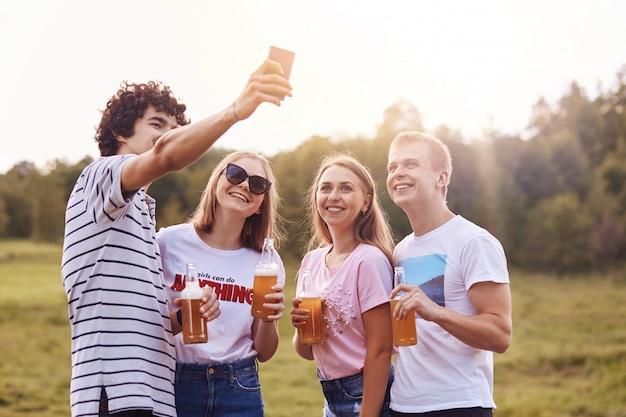 Amigos felices beben bebidas energéticas, posan para selfie