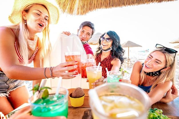 Amigos felices bebiendo en el bar de cócteles de playa con mascarillas