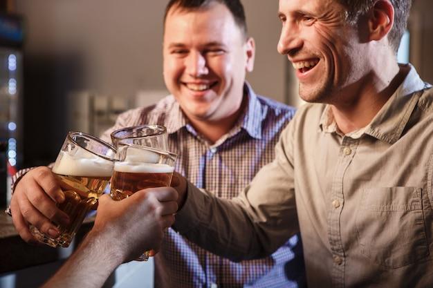 Amigos felices bebiendo cerveza en el mostrador en pub