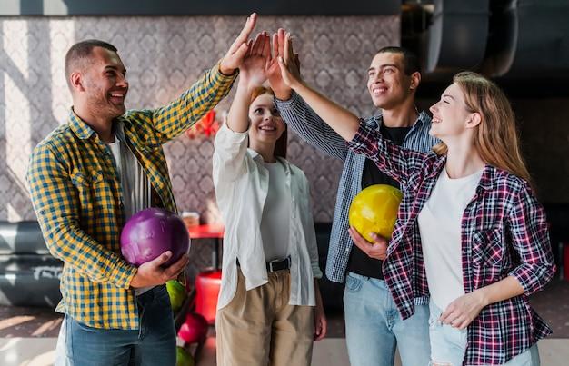 Amigos felices con bolas de boliche en un club de bolos