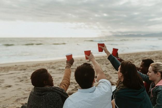 Amigos felices brindando en la playa