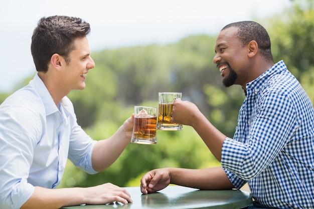 Amigos felices brindando vasos de cerveza