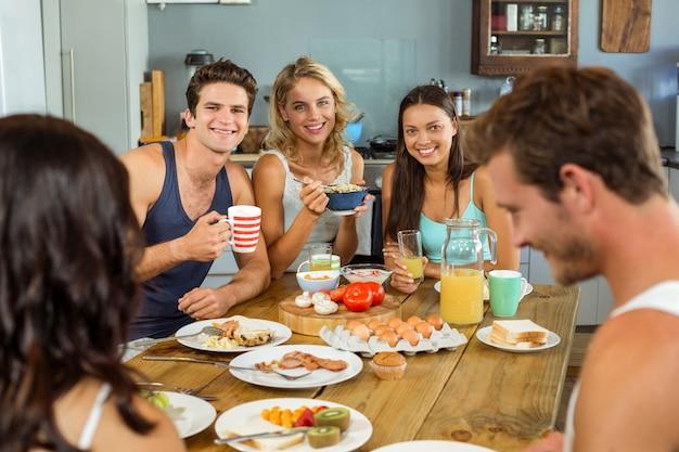 Amigos felices buscando pareja mientras desayunando