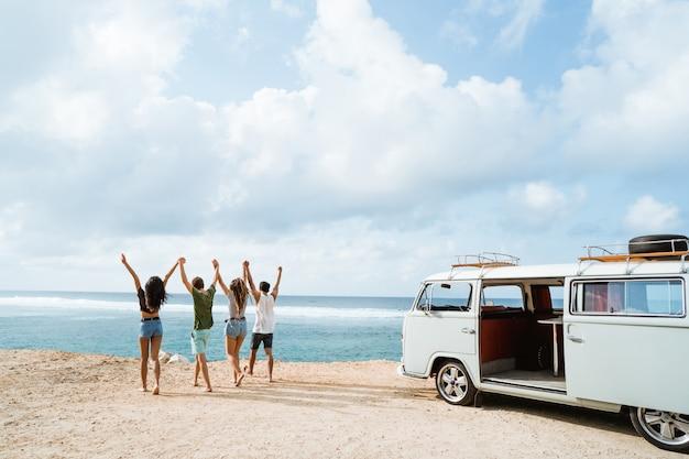 Amigos felices caminando en la playa y levantarse las manos