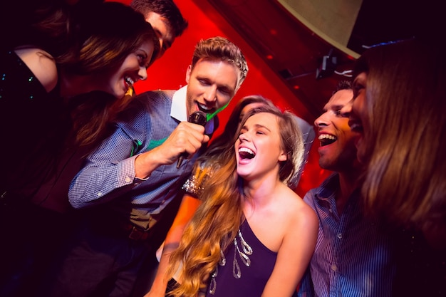 Amigos felices cantando karaoke juntos