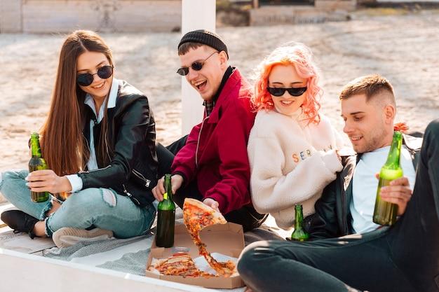 Amigos felices con cerveza y pizza en picnic
