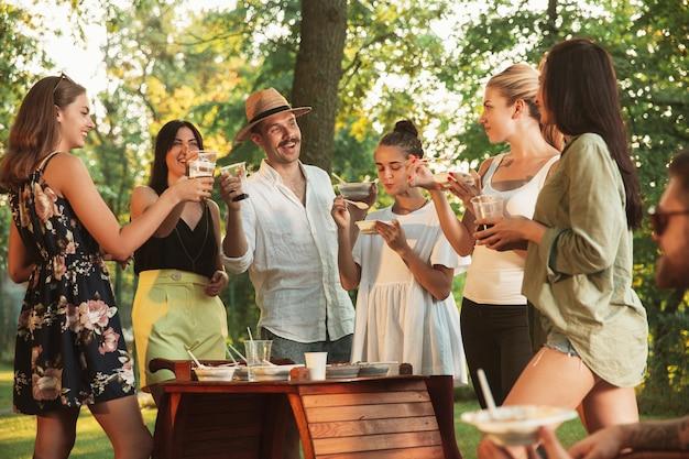 Amigos felices comiendo y bebiendo cervezas en la cena de barbacoa al atardecer