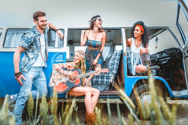 Amigos felices conduciendo una minivan vintage