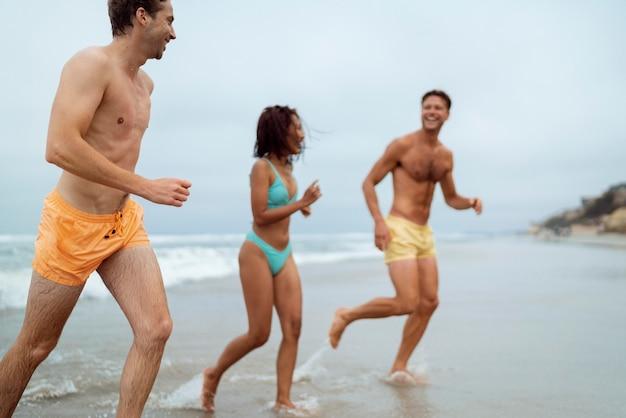 Amigos felices corriendo en la playa de tiro medio
