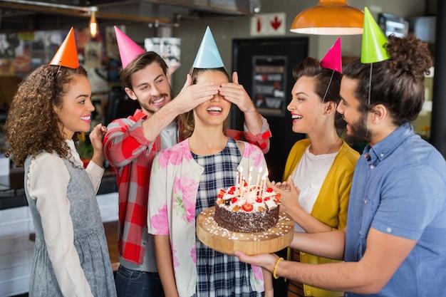Amigos felices dando sorpresa a la mujer durante su cumpleaños