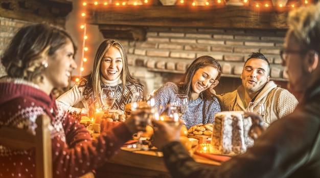 Amigos felices degustando comida dulce de navidad en casa fiesta divertida