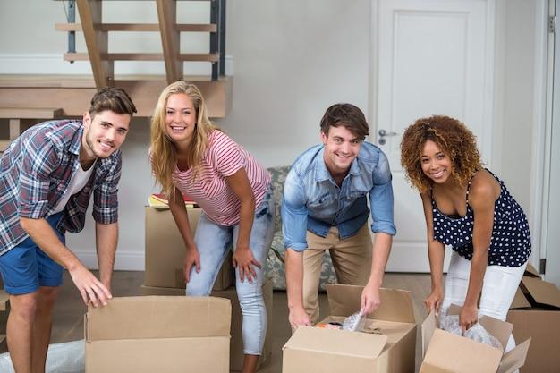 Amigos felices desempacando cajas en casa nueva