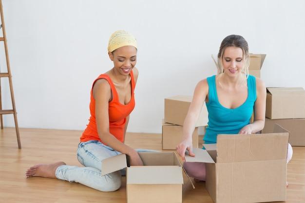 Amigos felices desenvolviendo cajas en una casa nueva.