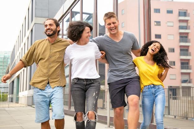 Amigos felices y despreocupados caminando afuera y divirtiéndose