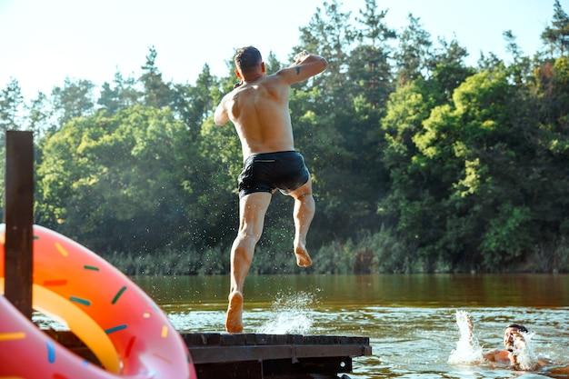 Amigos felices divirtiéndose, saltando y nadando en el río