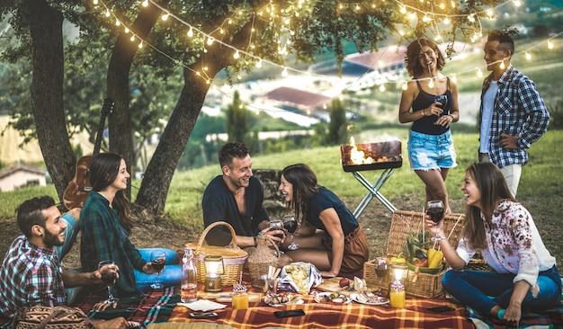 Amigos felices divirtiéndose en el viñedo después del atardecer