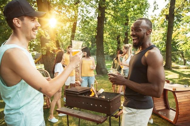 Amigos felices están tomando cerveza y fiesta de barbacoa en un día soleado