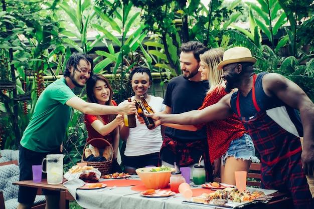 Amigos felices con fiesta de barbacoa en la naturaleza.