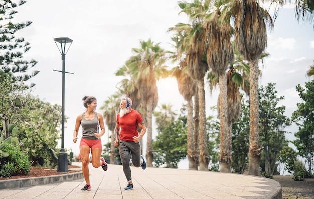 Amigos felices del gimnasio corriendo al atardecer al aire libre